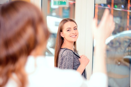 good bye: Welcome to our salon again. Rear view of hairdresser saying good bye and waving her hand to her satisfied client in the beauty salon