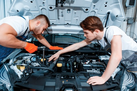 They can fix anything. Two handsome car mechanics in uniform checking the engine under hood in the car service station Stock Photo