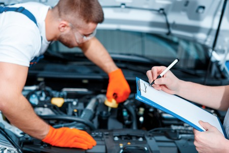 car service station: Running diagnostics. Two handsome car mechanics in uniform checking the engine under hood in the car service station and checking in service order
