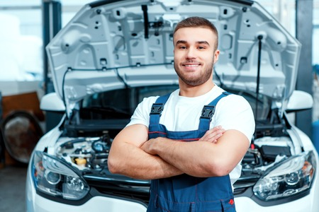 car mechanic: Welcome to our service station. Portrait of a smiling handsome mechanic in uniform posing by the car at car service station with his hands crossed
