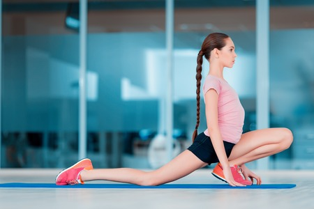 fit girl: Practicing yoga. Beautiful teenage girl in sports clothing training yoga position on the mat in health club