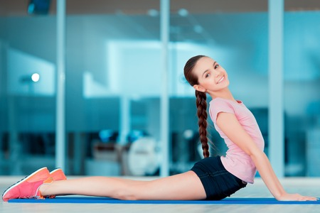 Sports training. Beautiful teenager in sports clothing training on yoga mat in health club