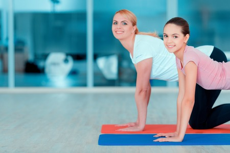 health conscious: Health conscious. Side view image of beautiful teenage girl and her mother in sports clothing training yoga on the mat in sports club