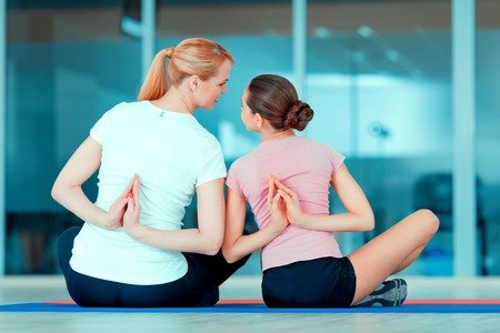 Family training. Rear view image of beautiful teenage girl and her mother in sports clothing training yoga on the mat in sports club
