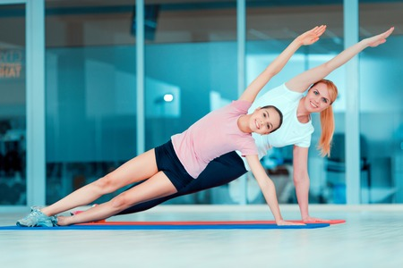 Finding inner peace and harmony. Beautiful teenage girl and her mother in sports clothing training yoga and taking similar positions on the mat in sports club