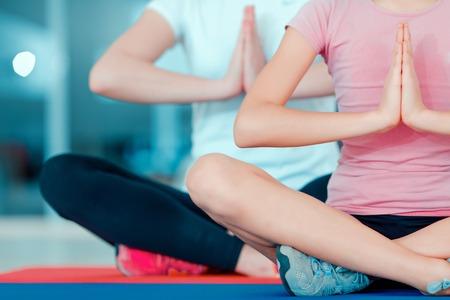 salud y deporte: Buscando nirvana. Recorta la imagen de una hermosa chica adolescente y su madre en la formaci�n de yoga ropa deportiva en el tapete en club deportivo Foto de archivo