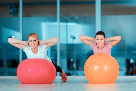 keeping fit: Keeping fit and feeling great. Beautiful teenage girl and her mother in sports clothing training on fitness balls against glass wall in sports club