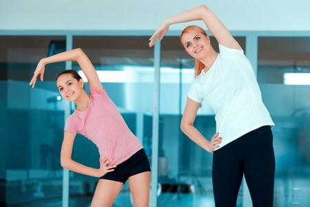one teenage girl only: Starting the workout. Beautiful mature woman and her teenage daughter in sports clothing exercising aerobics against glass wall in the gym