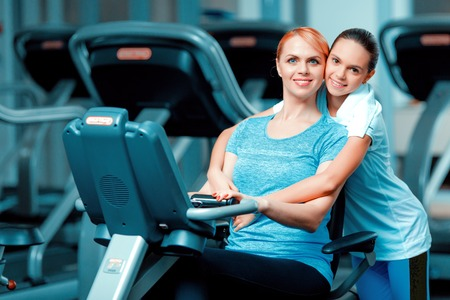 Training with mom. Beautiful mature woman bonding her teenage daughter in sports clothing after workout on exercise bicycle in the gym Stock Photo