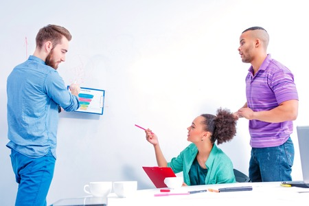 Confident and creative team. Group of cheerful business people in smart casual wear discussing data and writing on the board while having a brain storming in the meeting room