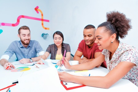 brain storming: Working hard to their creative goals together. Group of cheerful business people in smart casual wear discussing analytical infographics while having a brain storming in the meeting room Stock Photo