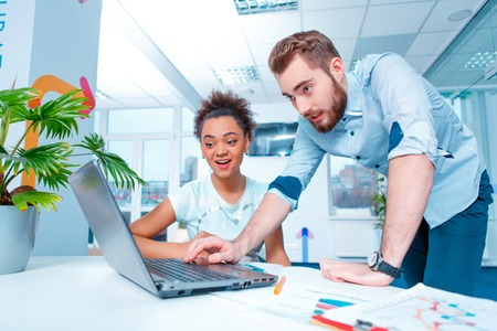 Creative team at work. Young African woman and Caucasian man in smart casual looking at laptop together while sitting in creative space Stock Photo