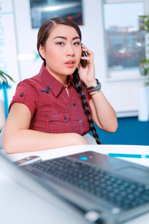Studying in digital age.  Portrait of young chinese woman in casual clothing talking over the mobile phone while sitting in creative space with her laptop photo