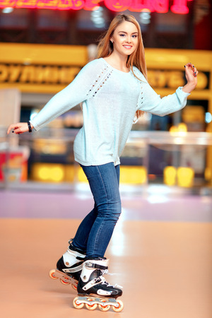 blading: Active leisure is what I like. Beautiful female teenager with long hair having skating on the rollerdrome