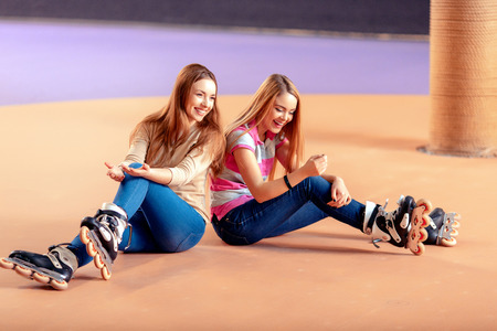 rollerblades: Fun on the skating rink. Two beautiful teen girls sitting on the rollerdrome wearing rollerblades and smiling