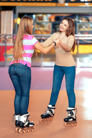 inline skater: Best friends ever. Two beautiful girls having fun on the roller rink playing and laughing to each other
