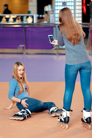 too fast: It was too fast for me. Two beautiful teen girls having fun on the skating rink while one girl sitting on the floor jokingly stretching her hands to her friend who makes photo on her smart phone