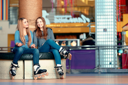 rollerblade: Weekend fun. Two beautiful teen girls having fun on the skating rink while sitting and talking emotionally