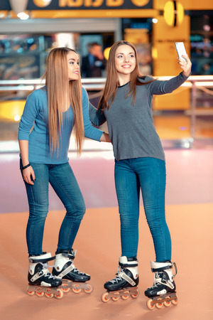 happy moment: Happy moment with der friend. Two beautiful teen girls having fun on the skating rink and making selfie on the smart phone