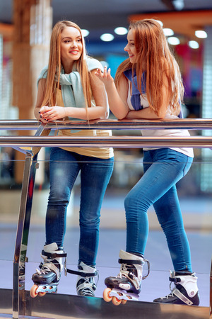 blading: It is never boring when ewe are together. Two beautiful teen girls in casual clothing having fun on the skating rink and talking