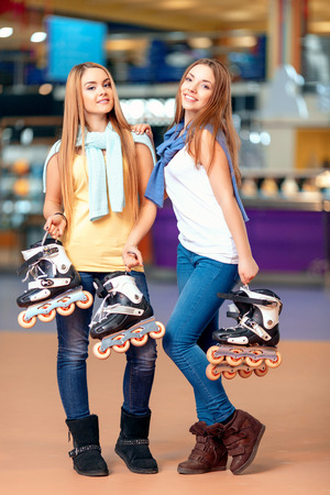 blading: After skating. Cute young girsl posing on the skating rink and holding roller blades Stock Photo