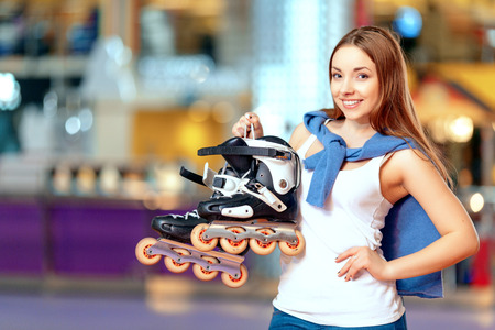 blading: Young and active teen. Cute young girl posing on the skating rink holding her rollerblades and smiling at camera