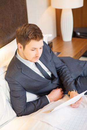 Negocios en el camino. Vista superior de joven empresario confía en traje y corbata lectura de documentos mientras se está sentado en la cama en la habitación de hotel de lujo