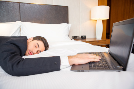 keeping room: Tired and overworked. Exhausted business man in formalwear sleeping on the bed of the luxury hotel room keeping his hand on laptop keyboard Stock Photo
