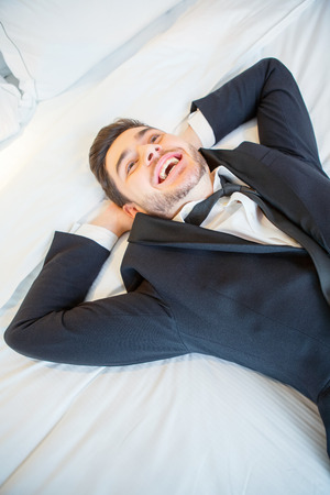 keeping room: Happy after the hard day. Smiling handsome businessman lying on the bed of luxury hotel room and keeping his hands above his hands