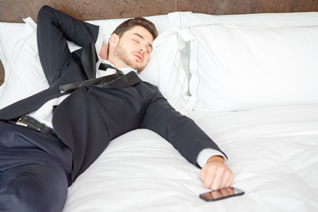keeping room: Tired and overworked. Exhausted business man in formalwear sleeping on the bed of the luxury hotel room keeping his hand on mobile phone Stock Photo
