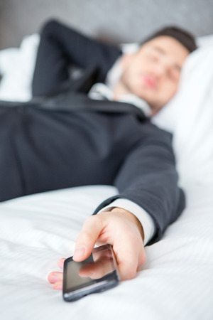 keeping room: Tired and overworked. Closeup of exhausted businessman in formalwear sleeping on the bed of the luxury hotel room keeping his hand on mobile phone