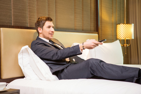 Having a break. Confident businessman in suit using remote control while sitting in the room of luxury hotel on the bed