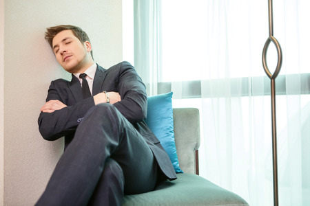 lag: Tired and overworked. Closeup of exhausted businessman in formalwear sleeping while sitting in the sofa of the luxury hotel Stock Photo