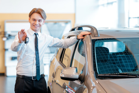 test drive: Make a test drive. Young handsome sales consultant standing by the new car in the showroom and showing keys Stock Photo