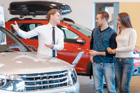 characteristics: This model has many great features. Young energetic salesman telling to the nice-looking customers about characteristics and features of the new car displayed at the showroom