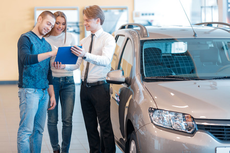 Gewoon aanmelden van de papieren en de auto is van jou. Knappe jonge verkoper die een klembord, zodat mannelijke klant kan zich aanmelden de papieren om een nieuwe auto te kopen Stockfoto