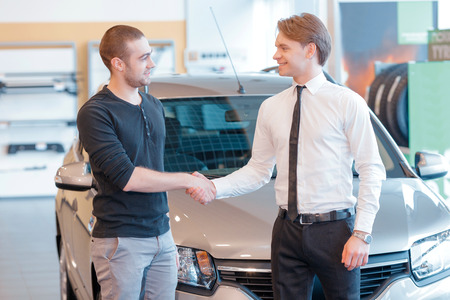 bonnet up: Done deal. Male customer shaking hands with a young smiling sales consultant in showroom with a new car and showroom view on the background in blurry