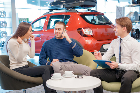 automobile dealership: Just imagine  we bought a car. Young male customer talking over the phone and female customer showing delight about the purchase of the car with the sales consultant by the table and a blurred red showroom car on the background