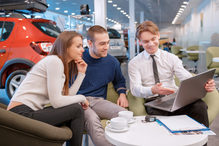 Das neue Fahrzeug wird genau das gleiche sein. Verkaufsberater, die auf die lächelnde Paar Informationen über ihr neues Auto auf dem Bildschirm des Laptops mit Blick auf den Showroom auf dem Hintergrund