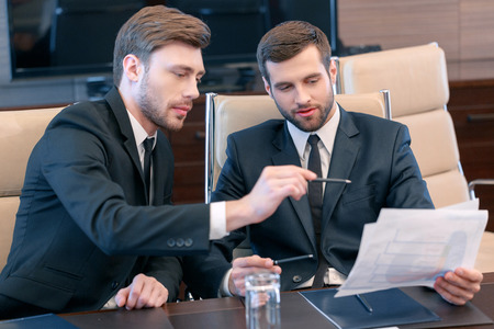 solution: Smart solutions for business. Two good-looking managers in black suits looking at the business data and discussing business trends Stock Photo