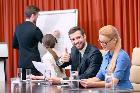 Buen trabajo. Hombre de negocios en traje negro clásica pinta un cuadro en el rotafolio mientras que sus colegas mujeres se dieron la vuelta para ver a su imagen y su pareja masculina sonríe y muestra su pulgar hacia arriba