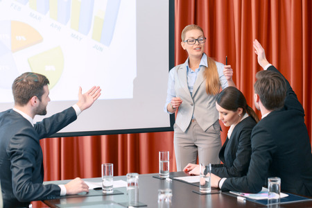 actively: Active discussion. Participants of the business meeting actively gesture and raise hands discussing data on the screen Stock Photo