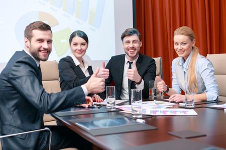 competencias laborales: Grandes compa�eros de trabajo. Los profesionales de negocios levantan sus pulgares arriba sonriendo y deleitarse con el resultado de la reuni�n