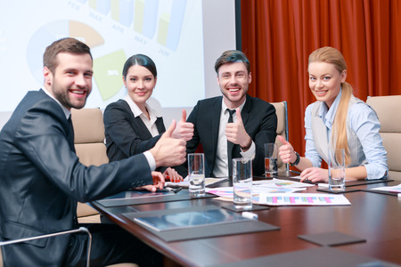 great job: Great job colleagues. Business professionals raise their thumbs up smiling and being delighted with the result of the meeting Stock Photo