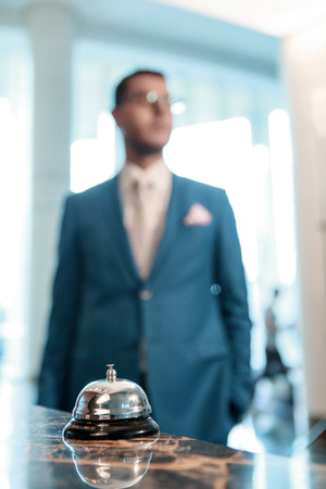 silver service: Hotel welcomes you. Selective focus of modern luxury hotel reception desk with silver service bell and blurry silhouette of a businessman approaching the reception Stock Photo
