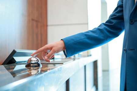 hostel: Service, please. Closeup of a businessman hand ringing silver service bell on hotel reception desk Stock Photo