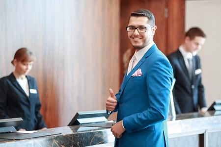 Legjobb szállodai szolgáltatás. Jó megjelenésű üzletember klasszikus kék öltönyt mutató hüvelykujjával felfelé eléri a recepciónál két recepciós a háttérben