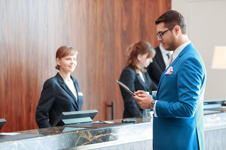 Looking for check-in information. Young handsome businessman in classical blue suit looks at his tablet device standing just in front of the hotel reception desk where young receptionists welcomes him with  a smile