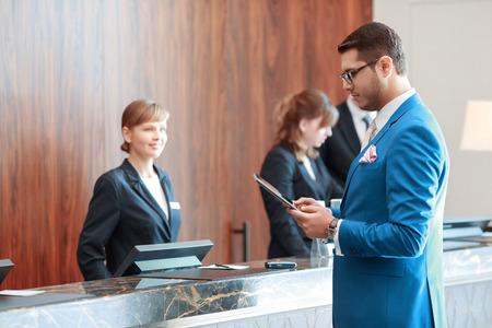 recepcion: Buscando informaci�n de check-in. Apuesto hombre de negocios joven en traje azul cl�sico mira a su dispositivo de tableta de pie justo en frente de la recepci�n del hotel donde recepcionistas j�venes le da la bienvenida con una sonrisa