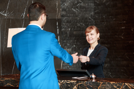 passing over: Welcome at our hotel. Selective focus of a beautiful female receptionist passing over a key to the guest who checks-in at a reception desk